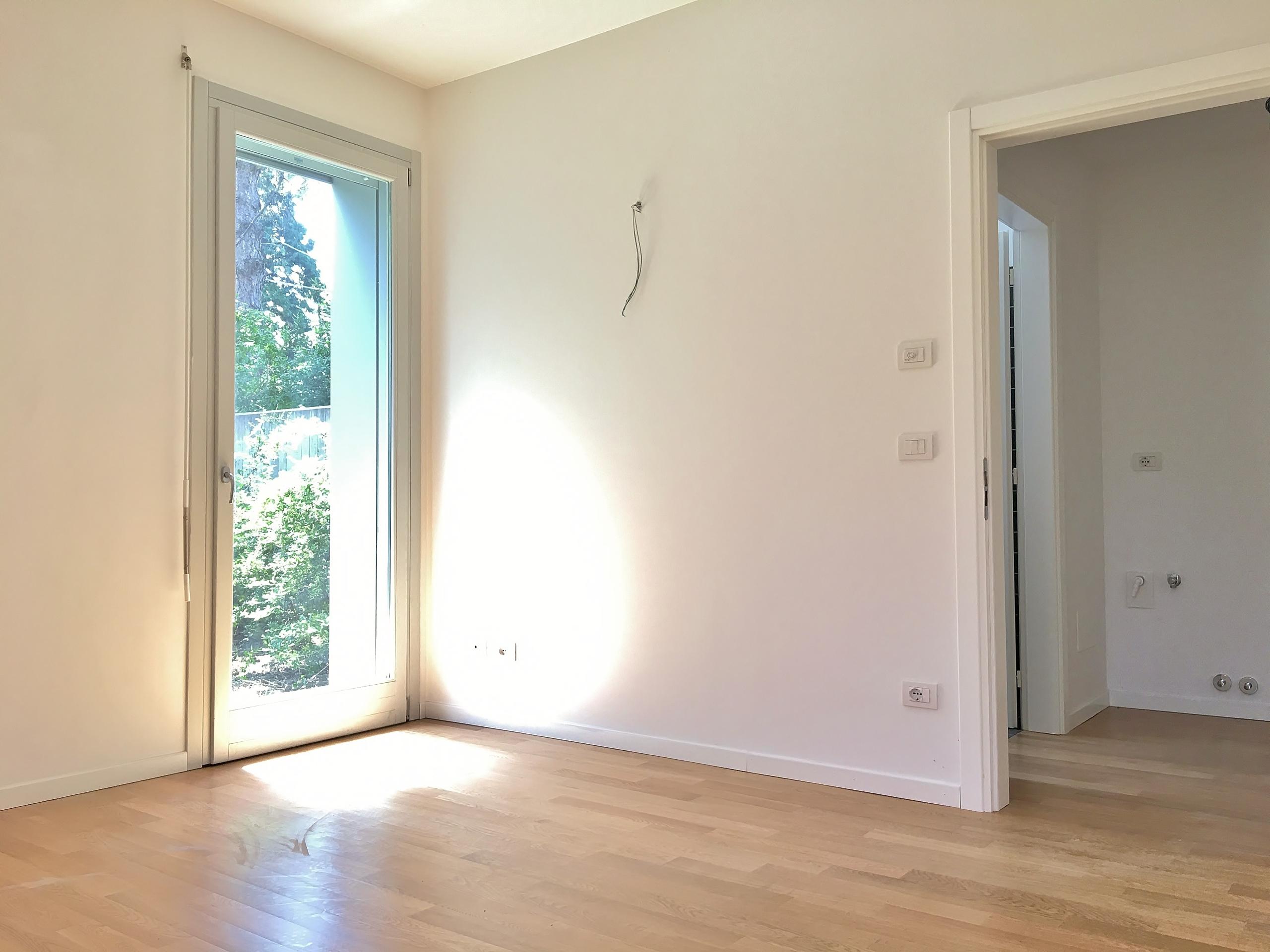 Particolare della camera da letto; la porta-finestra sul giardino privato